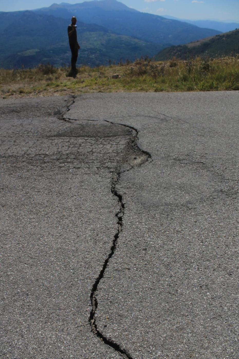 La fenditura, provocata dal terremoto, che ha inciso la strada asfaltata che da Forca di Presta raggiunge Pretare, sullo sfondo alcune frazioni di Arquata del Tronto colpite dal sisma.